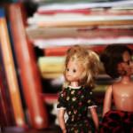 Zwei Puppen sitzen im Bücherregal.